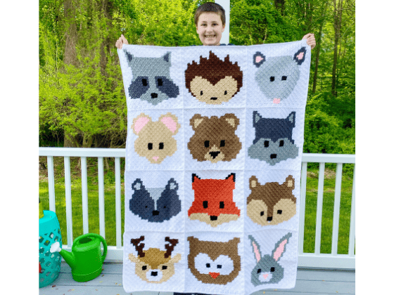 a kid holding a crochet blanket with crocheted woodland animals